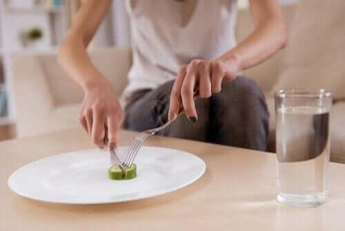 Kvinde, der spiser agurk, oplever spiseforstyrrelser som et advarselstegn på psykisk sygdom