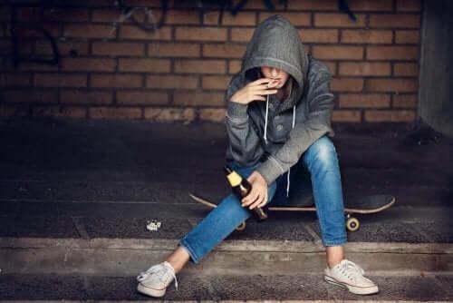 Person med cigaret i munden sidder på skateboard