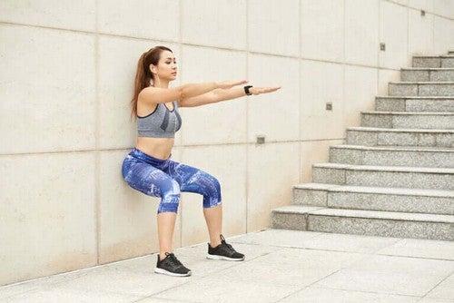Kvinde laver squats op ad væggen