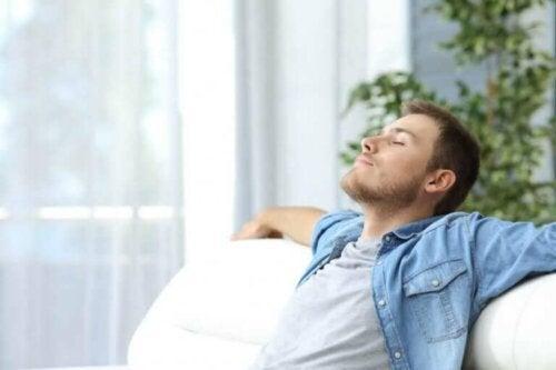 Afslappet mand i sofa anvender afslapningsteknikker