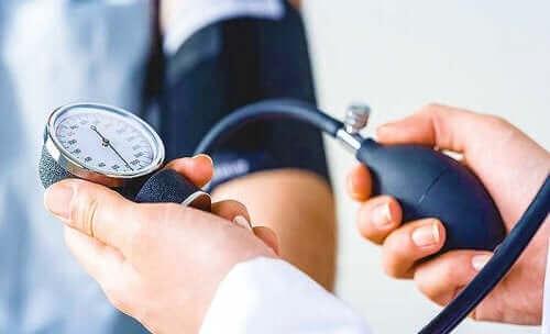 Vitaminerne i fed fisk hjælper med at kontrollere blodtrykket, som her måles af en læge