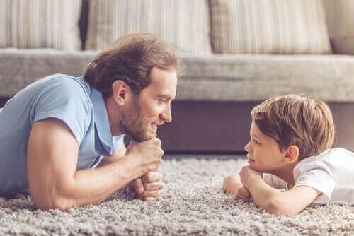 Far ligger på gulv med søn