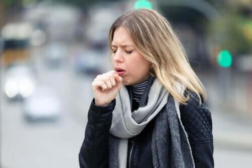 Kvinde står på gaden og hoster