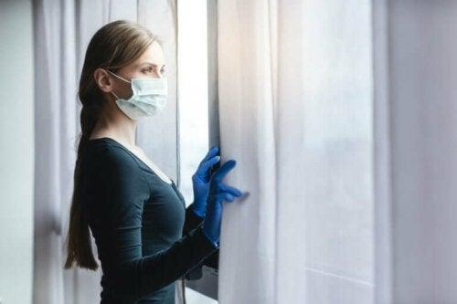 Kvinde med mundbind står ved vindue som et resultat af at holde afstand under lockdown