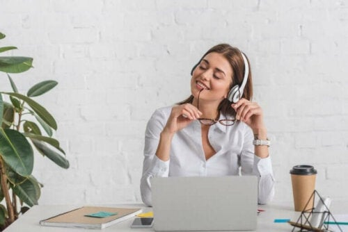 Kvinde smiler ved skrivebord med computer