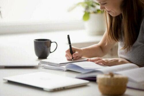Kvinde skriver i en bog, da hun arbejder hjemmefra