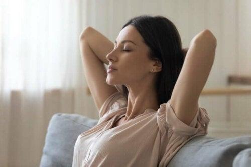 Kvinde i sofa slapper af ved hjælp af afslapningsteknikker