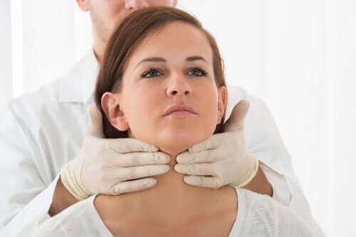 Læge tjekker kvindes hals