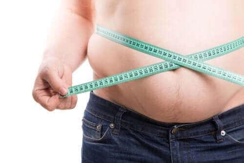 Mand måler mave med målebånd
