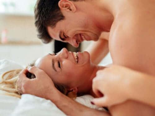 Mand og kvinde griner i seng