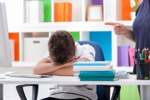 Søvnforstyrrelser hos børn illustreres af træt dreng, der hviler hoved på arme