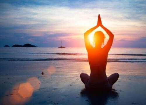 Person mediterer på strand for at vedligeholde god mental sundhed