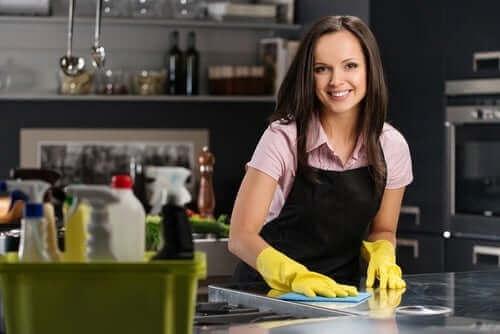 En kvinde, der bruger affedter til at fjerne pletter i køkkenet
