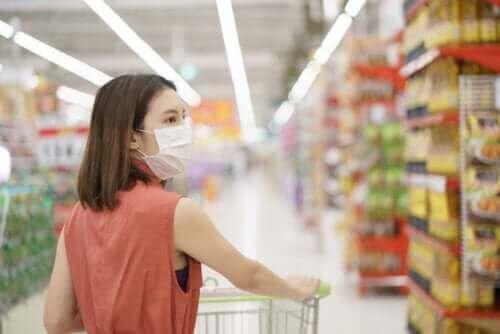 Kvinde handler i supermarked med mundbind på