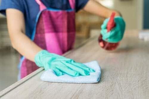 En kvinde, der vil bruge affedter til at fjerne pletter på træbord