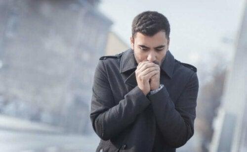 Mand fryser og puster på hænder