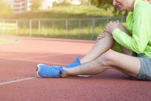 Mand på tennisbane tager sig til knæ