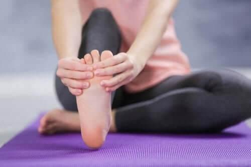 Kvinde laver strækøvelser for at reducere hævede fødder og ankler