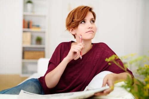 Kvinde sidder med avis og blyant