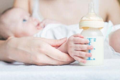 Baby med sutteflaske med korrekt suttehoved for at undgå luft i maven