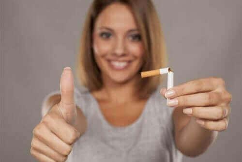 En kvinde, der viser en knækket cigaret