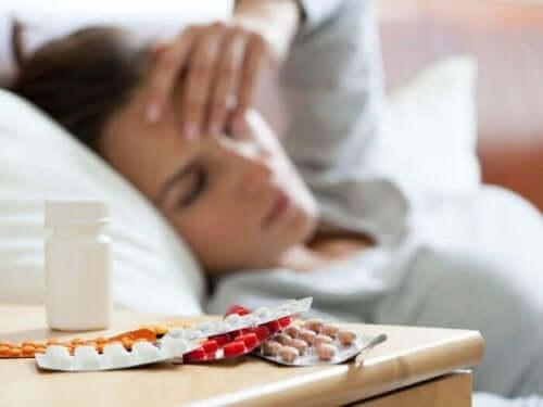 Kvinde med hovedpine og piller på sengebord
