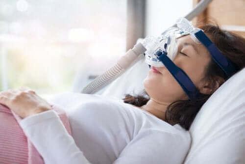 Kvinde med CPAP maskine til at kontrollere snorken