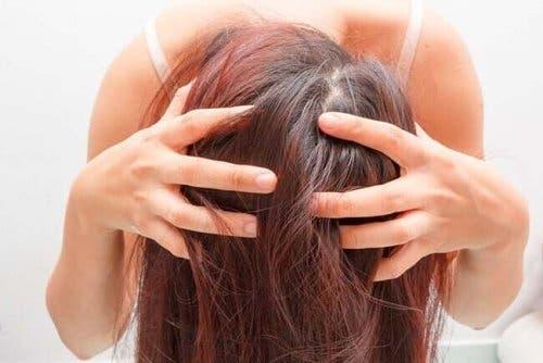 Kvinde bruger rosmarin for sundt hår