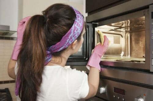 Kvinde er ved at rengøre ovnen