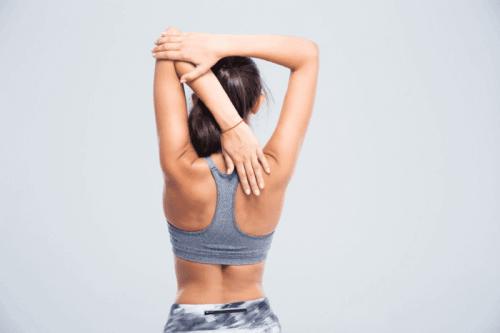 Kvinde strækker ud i skuldrene