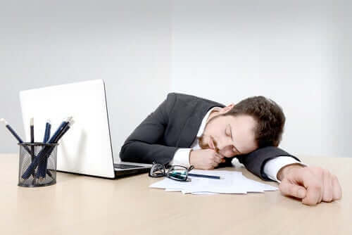 Mand sover på skrivebord som eksempel på de forskellige typer af søvnløshed