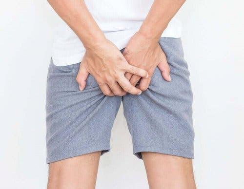 Blod i afføringen kan være smertefuldt, hvilket illustreres af mand, der tager sig til bagdel
