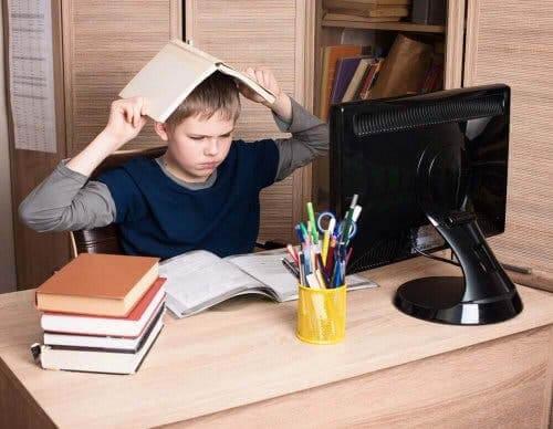 Sur dreng med bøger ved computer