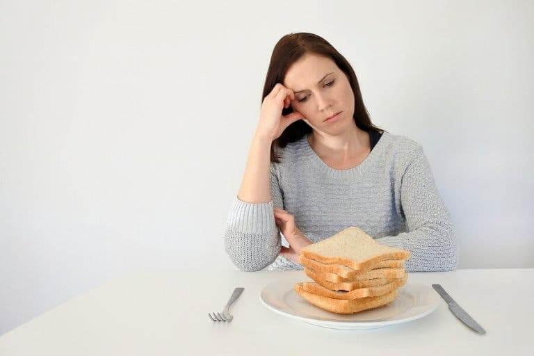 Kvinde ser trist på hvidt brød