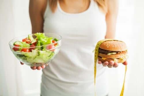 Kvinde holder burger og salat i hænderne
