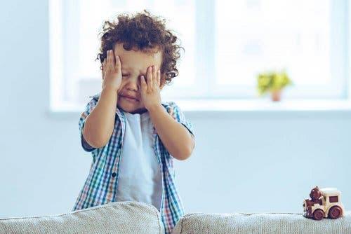 Dreng græder og tager sig til ansigt