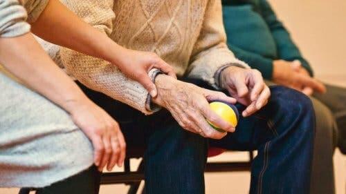 Person holder ældre mand i hånden