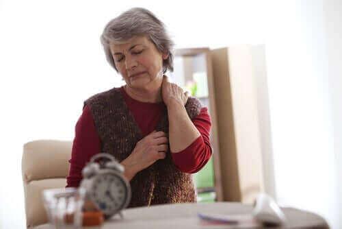 Kvinde tager sig til nakke grundet smerte