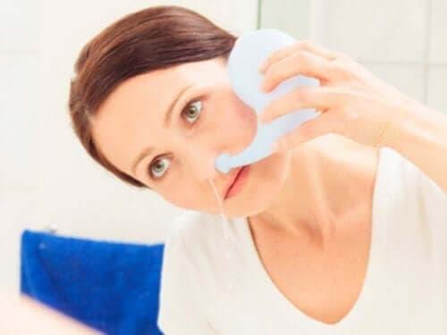 Kvinde skyller sin næse med vand
