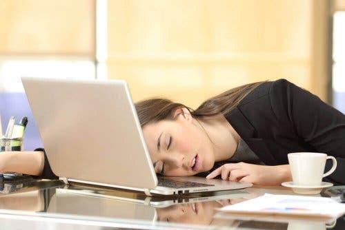 Kvinde sover på skrivebord