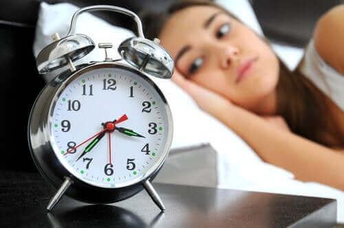 Kvinde ligger vågen i seng og ser på vækkeur