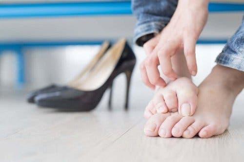 Kvindes fødder ved siden af højhælede sko