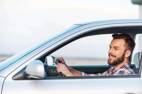 Smilende mand kører bil