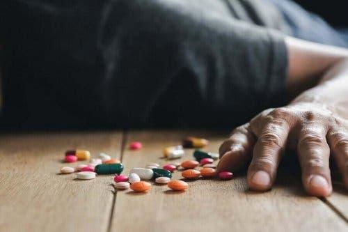 Mand på gulv med piller oplever medicinforgiftning