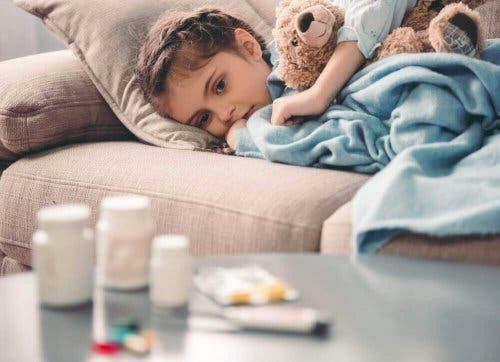 Pige på sofa med medicin på sofabordet