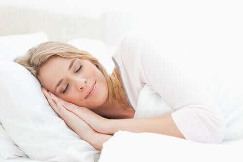 Smilende kvinde sover efter at have fulgt sunde sovevaner