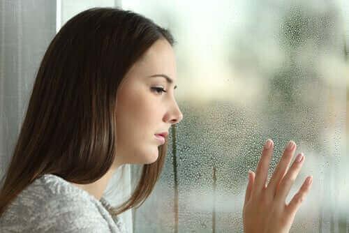 Kvinde ved vådt vindue lider af ferie blues