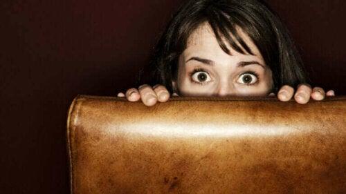 Kvinde gemmer sig bag lænestol