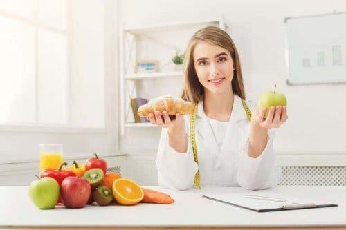 Ernæringsekspert sidder med friske frugter for at opmuntre til at mindske indtaget af sukker