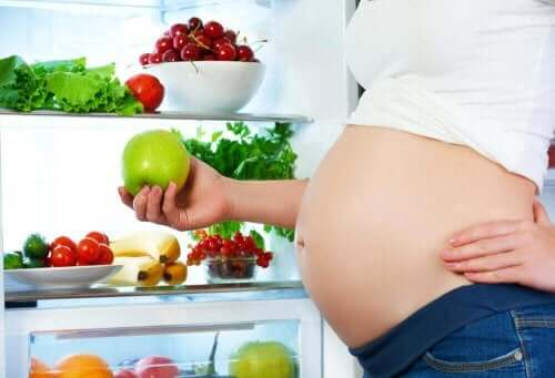 Kost under graviditet illustreres af gravid kvinde ved fyldt køleskab